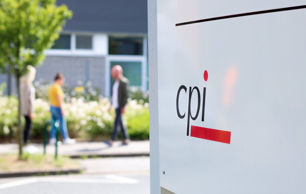 Zwei Frauen und ein Mann spazieren vor dem CPI Gebäude