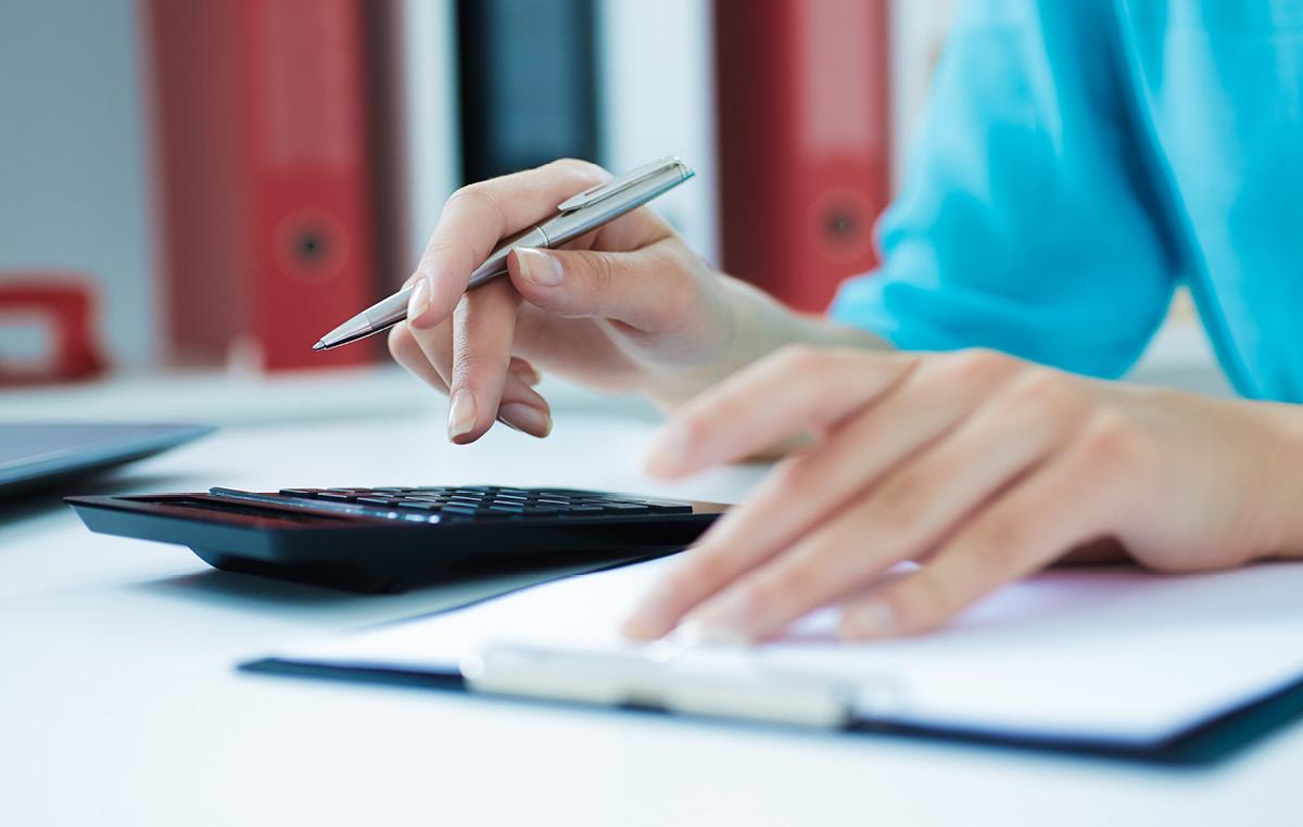 Frau benutzt Taschenrechner am Schreibtisch