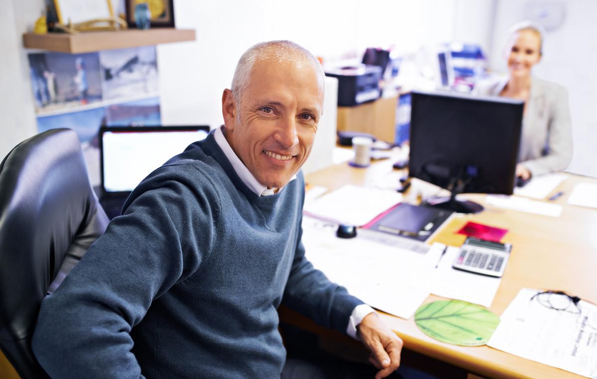 Lächelnder Mann an seinem Arbeitsplatz im Büro
