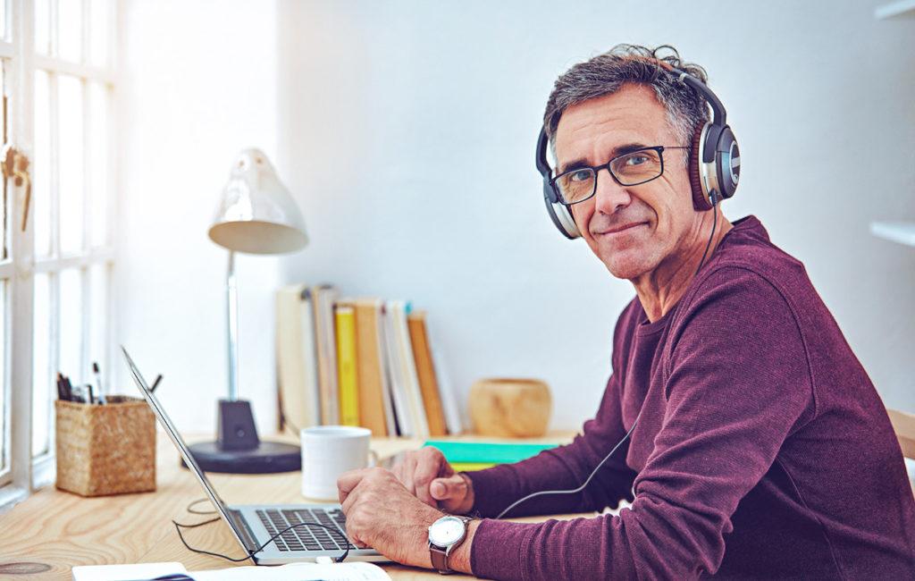 Mann lernt von Zuhause mit Laptop und Kopfhörern