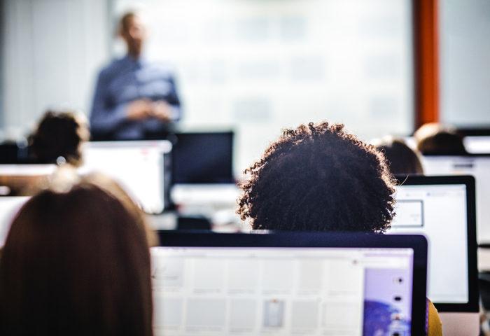 Schüler sitzen vor dem Rechner und hören Dozenten zu