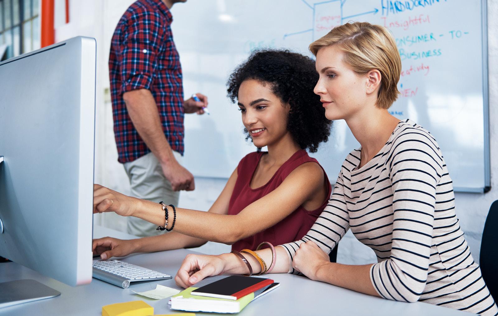 Zwei Frauen lernen gemeinsam am PC und ein Mann im Hintergrund schreibt auf das Whiteboard